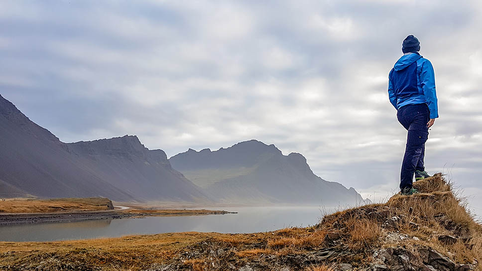 A young man wearing blue jacket stands at the edge of a headland, overlooking a magnificent fjord covered with a light mist. Tall mountains emerge from the sea water. Grass is turning gold.