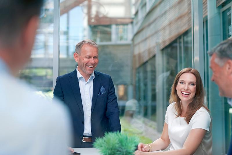 Fokus på to kollegaer rundt et bord - der hvor den ene smiler til kameraet