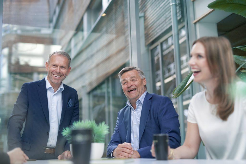 Tre kollegaer rundt et bord deler en god latter og smil