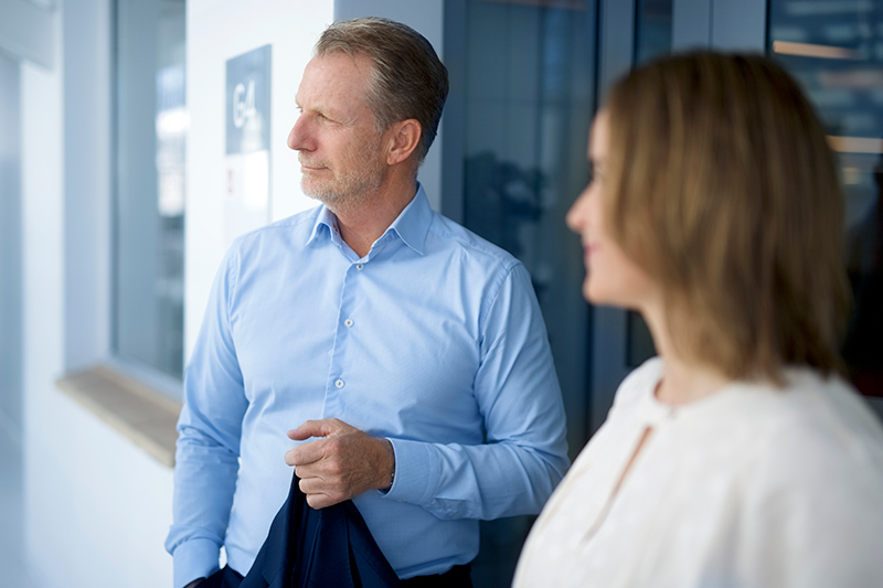 Bilde av to kollegaer, med fokus på den ene som ser utover rommet og holder jakken i høyre hånd