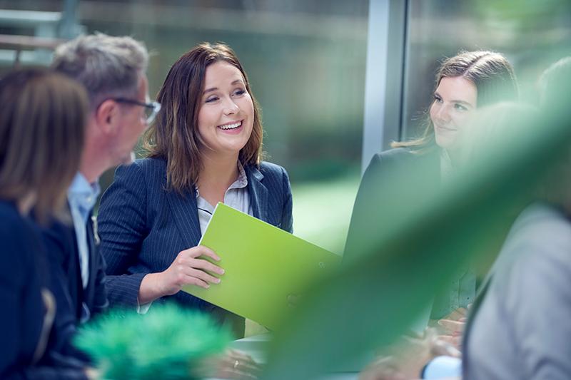 Kvinnelig kollega i samtale med bok i hånden